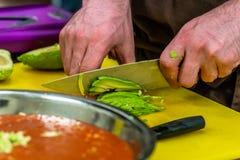 Cozinheiro chefe masculino Slicing Avocado para a refeição do casamento imagem de stock