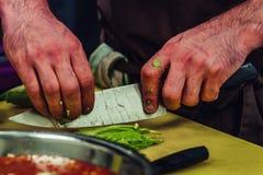 Cozinheiro chefe masculino Slicing Avocado para a refeição do casamento - a cozinha ajustou-se com ação, somente as mãos do cozin fotos de stock