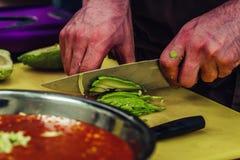 Cozinheiro chefe masculino Slicing Avocado para a refeição do casamento - a cozinha ajustou-se com ação, somente as mãos do cozin foto de stock