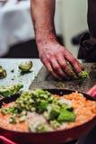 Cozinheiro chefe masculino Slicing Avocado para a refeição do casamento fotografia de stock royalty free
