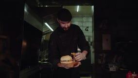 Cozinheiro chefe mestre de sorriso no uniforme que olha a câmera, guardando a placa com hamburguer servido filme