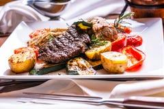 Cozinheiro chefe na cozinha do hotel ou do restaurante que cozinha somente as mãos Bife preparado com decoração vegetal imagens de stock