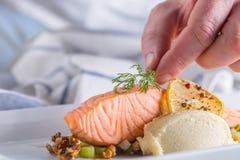 Cozinheiro chefe na cozinha do hotel ou do restaurante que cozinha, somente mãos Bife salmon preparado com decoração do aneto imagem de stock royalty free