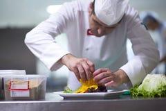 Cozinheiro chefe na cozinha do hotel que prepara e que decora o alimento Fotos de Stock