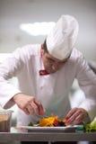 Cozinheiro chefe na cozinha do hotel que prepara e que decora o alimento Fotografia de Stock