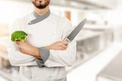 Cozinheiro chefe na cozinha do restaurante com brócolis e faca nas mãos Fotografia de Stock