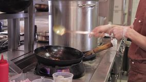 Cozinheiro chefe na cozinha do restaurante no fogão com a bandeja do frigideira chinesa, fazendo o flambe no alimento filme