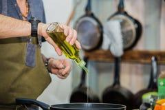 Cozinheiro chefe na cozinha do restaurante no fogão com a bandeja que adiciona o óleo imagem de stock