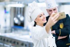 Cozinheiro chefe na cozinha e seu assistente novo que toma o selfie foto de stock royalty free