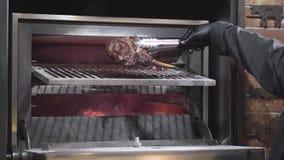 Cozinheiro chefe nas luvas pretas que abrem a grade do forno, em que estão preparando o reforço fritado para o lançar ao outro la vídeos de arquivo