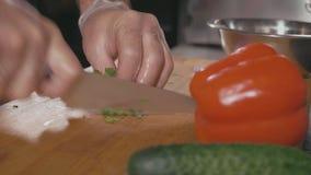 Cozinheiro chefe nas luvas que desbastam alguma salsa na placa de corte, fim acima filme