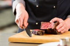 Cozinheiro chefe no cozimento da cozinha do hotel ou do restaurante imagens de stock royalty free