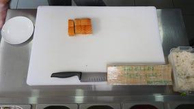 Cozinheiro chefe no restaurante que prepara e que corta o alimento saudável dos rolos de sushi Vista superior filme