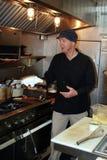 Cozinheiro chefe no trabalho na cozinha pequena Fotos de Stock Royalty Free