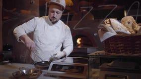 Cozinheiro chefe no uniforme branco e na luva de borracha que põem mexilhões na bandeja de alumínio com punhos usando tenazes de  video estoque