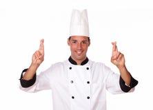 Cozinheiro chefe novo considerável que cruza seus dedos Fotografia de Stock Royalty Free