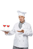 Cozinheiro chefe novo que guarda uma bandeja de dois vidros do vinho tinto Fotografia de Stock Royalty Free