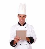 Cozinheiro chefe novo que trabalha com seu PC da tabuleta Foto de Stock Royalty Free