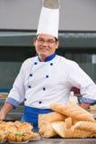 Cozinheiro chefe ou padeiro que levantam na frente das pastelarias Fotos de Stock