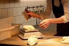 Cozinheiro chefe ou padeiro que pesam a massa na escala na padaria Imagem de Stock Royalty Free