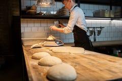 Cozinheiro chefe ou padeiro que pesam a massa na escala na padaria Imagens de Stock Royalty Free
