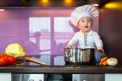 Cozinheiro chefe pequeno que cozinha na cozinha Imagens de Stock Royalty Free