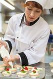 Cozinheiro chefe principal consideravelmente concentrado que prepara a sobremesa Imagem de Stock