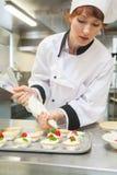 Cozinheiro chefe principal consideravelmente focalizado que prepara a sobremesa Imagem de Stock