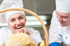 Cozinheiro chefe principal e seu levantamento assistente bonito foto de stock