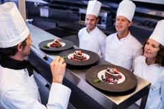 Cozinheiro chefe principal que inspeciona placas de sobremesa sobre na estação da ordem foto de stock royalty free
