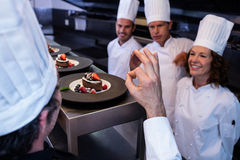 Cozinheiro chefe principal que mostra o sinal aprovado da mão após ter inspecionado placas de sobremesa fotos de stock