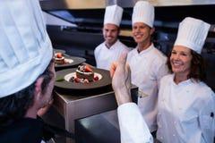 Cozinheiro chefe principal que mostra seus polegares acima após ter inspecionado placas de sobremesa foto de stock