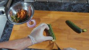 Cozinheiro chefe profissional nas luvas que cortam o pepino na placa de madeira na cozinha comercial imagens de stock royalty free