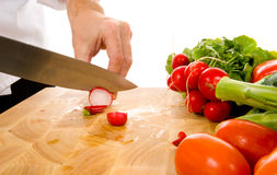 Cozinheiro chefe profissional que corta o radish Foto de Stock