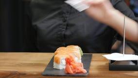 Cozinheiro chefe profissional que cozinha, trabalhando e preparando o alimento e o sushi asiáticos na cozinha do restaurante vídeos de arquivo