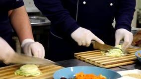 Cozinheiro chefe profissional que cozinha, trabalhando e preparando o alimento na cozinha do restaurante filme