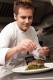 Cozinheiro chefe que adiciona o tempero ao prato no restaurante Fotografia de Stock