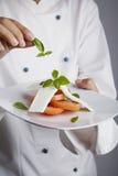 Cozinheiro chefe que adiciona verdes ao prato Imagens de Stock