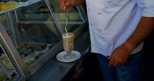 Cozinheiro chefe que agita o milk shake do chocolate com colher 4k vídeos de arquivo