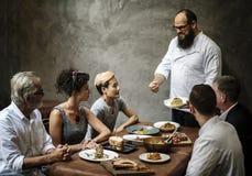 Cozinheiro chefe que apresenta o alimento aos clientes no restaurante fotografia de stock