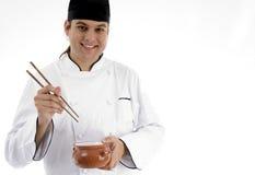 Cozinheiro chefe que apresenta o prato chinês com chopstick imagem de stock royalty free