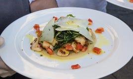 Cozinheiro chefe que apresenta o prato com marisco e queijo Imagens de Stock Royalty Free