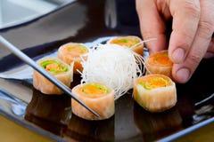 Cozinheiro chefe que arranja o prato do sushi Imagem de Stock