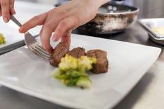 Cozinheiro chefe que chapeia acima do alimento em um restaurante fotos de stock royalty free