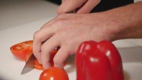 Cozinheiro chefe que corta acima um tomate com uma faca Fim acima filme