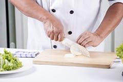 Cozinheiro chefe que corta a cebola Imagem de Stock Royalty Free
