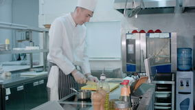 Cozinheiro chefe que corta o alho na placa de corte com uma faca e que mistura o com o sal trazido por um outro cozinheiro filme
