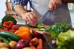 Cozinheiro chefe que corta o pepino com uma faca na placa de desbastamento Fotos de Stock
