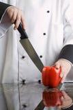 Cozinheiro chefe que corta a pimenta vermelha foto de stock