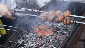 Cozinheiro chefe que cozinha a carne e os vegetais no assado no ar fresco, festival do alimento da rua filme